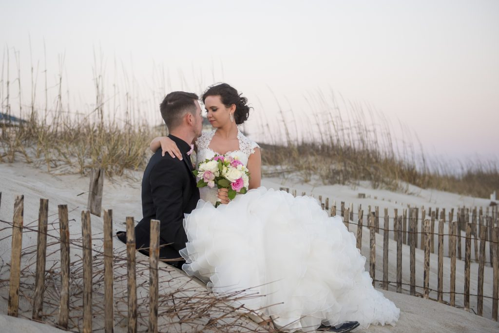 Bride sitting on grooms lap on sand dune at Celebration Cottage raleigh wedding photographer reviews
