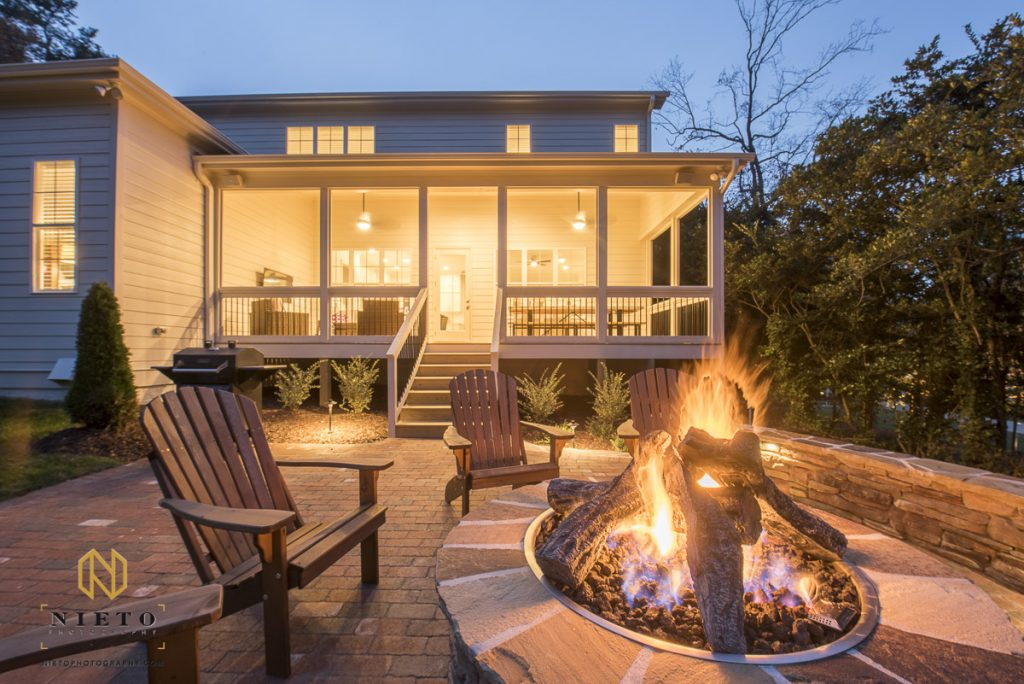 Real estate picture of a home exterior at night with fire pit
