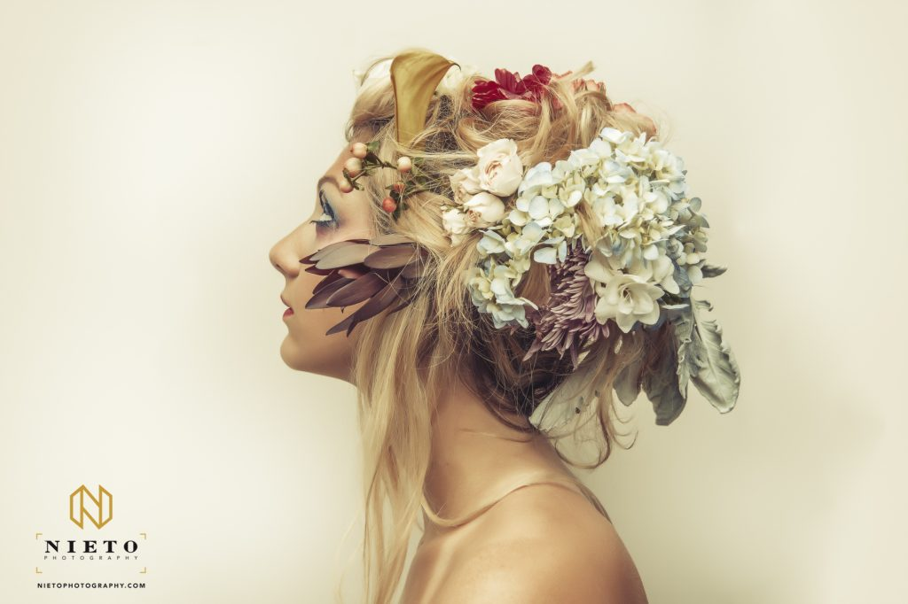 Model on white wall with large flower head piece