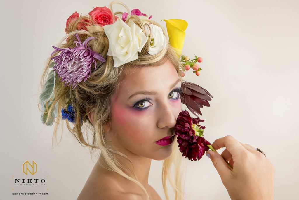model sniffing red flower with flowers in her hair