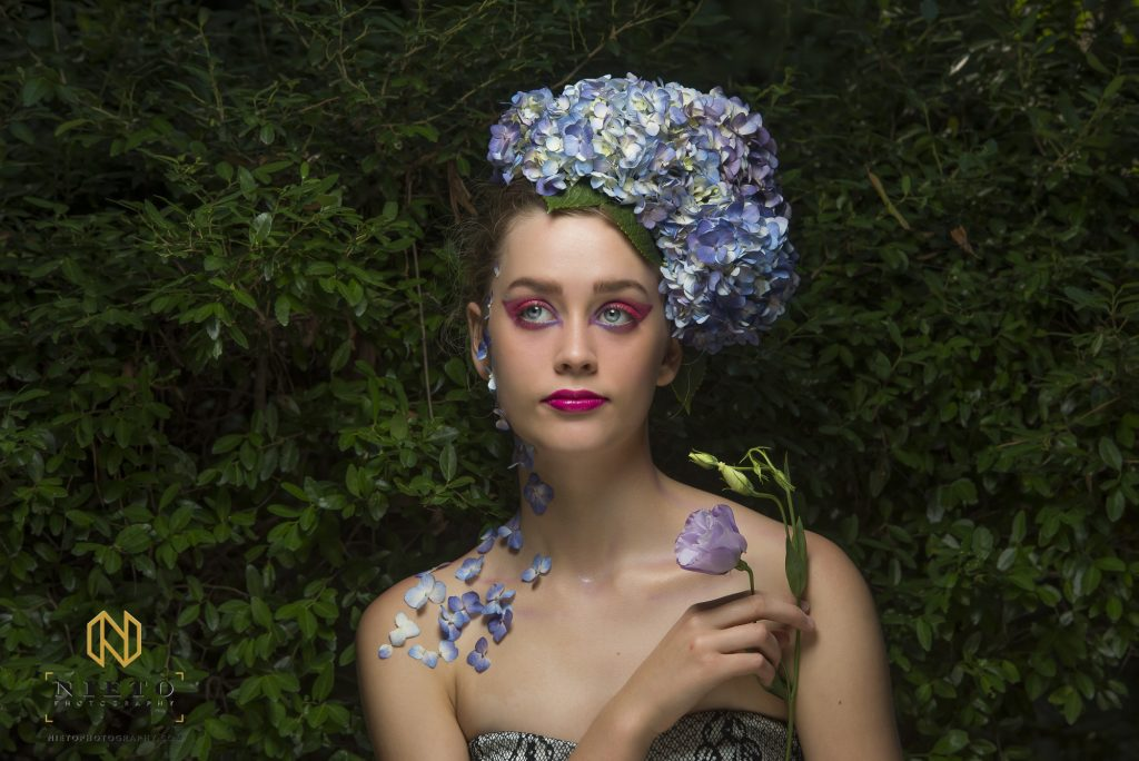 model holding purple flower while looking away from the camera