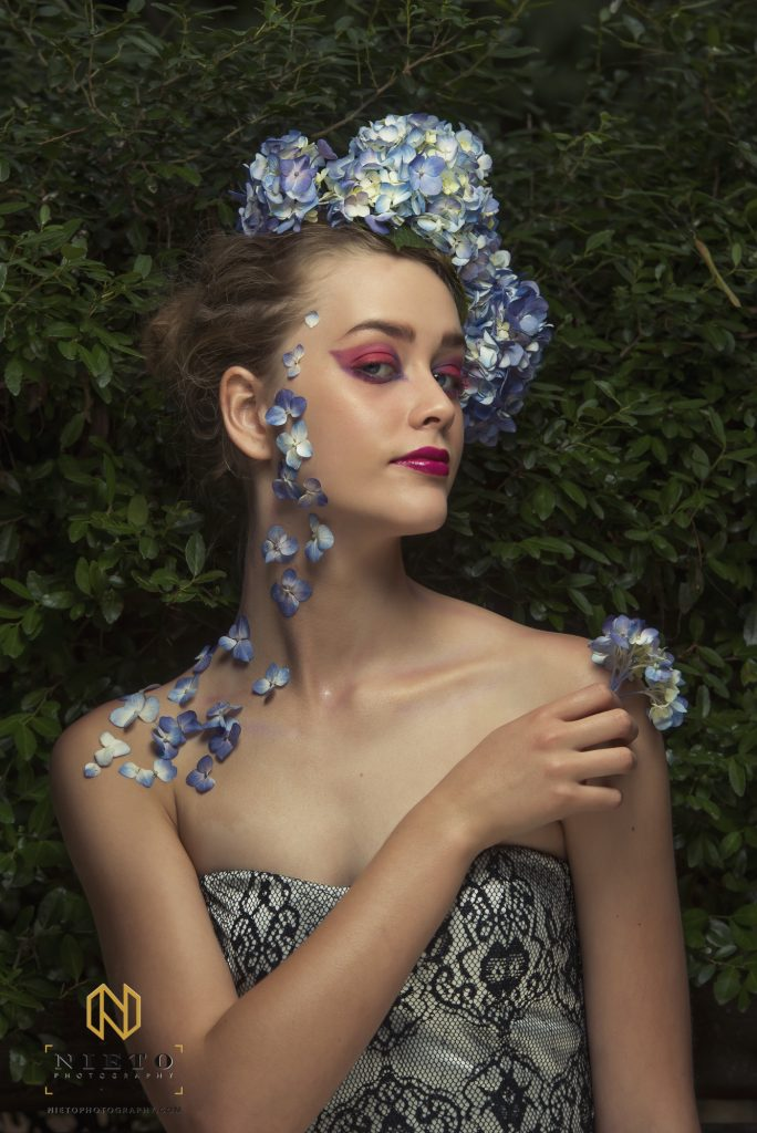 model with her back to a green bush and flowers on her neck and in her hair