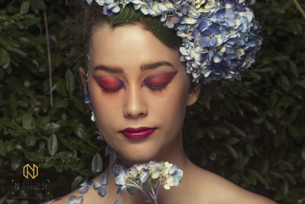 model with red and pink make up and flowers in her hair