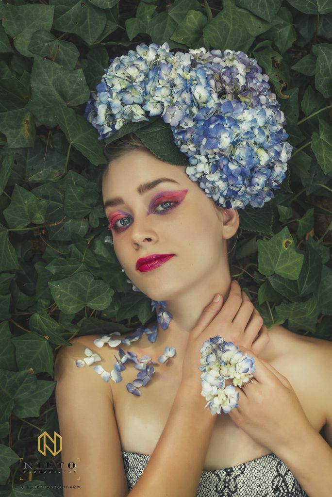 model looking at camera laying in ivy with flowers in her hair and in her hand