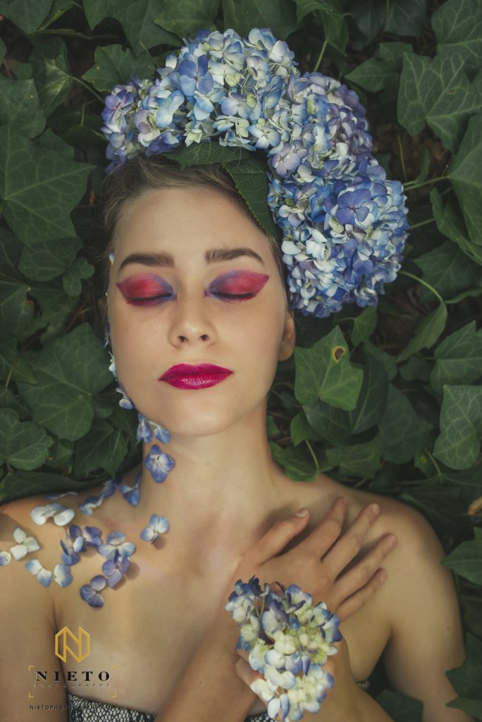 model laying back in ivy and flower in her hair and hand