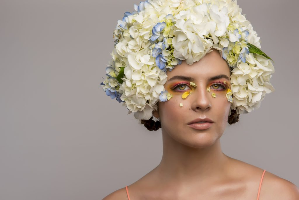 Model on gray background with floral headpiece