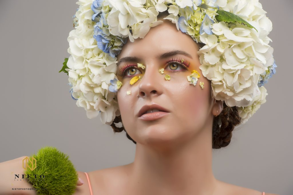 Model with hazel eyes and white flower head piece