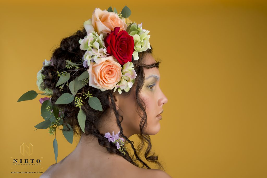 Model on orange background looking over her shoulder with flowers in her hair