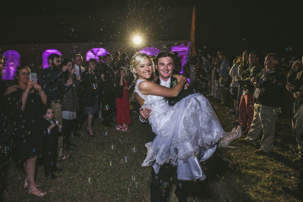 Groom carrying bride through bubble exit at night wedding