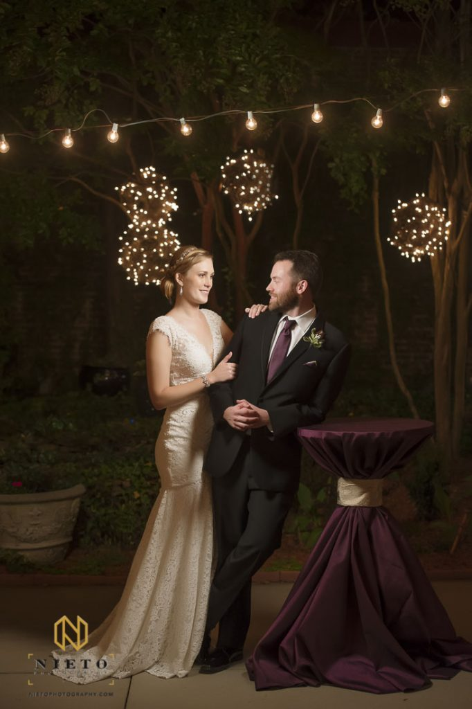 bride and groom on the patio of the Garden on Millbrook at night posing for a portrait as they look at each other