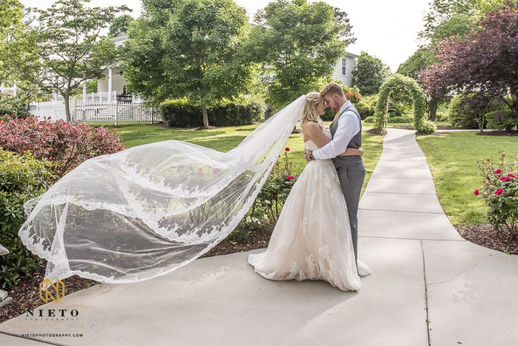 bride and groom kissing at the Hudson Manor as the brides veil blows in the wind