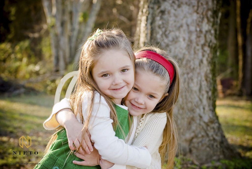 Sisters hugging each other tightly as the pose for their Raleigh family photographer