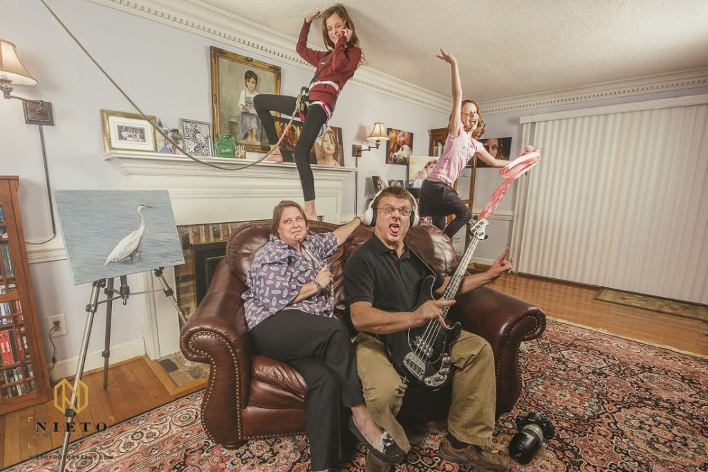 Family sitting on couch being silly for portrait