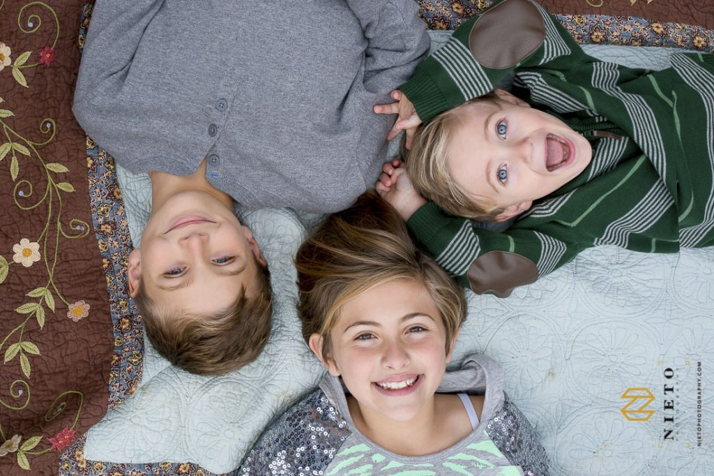two brothers and sisters laying on blanket smiling for the camera over head
