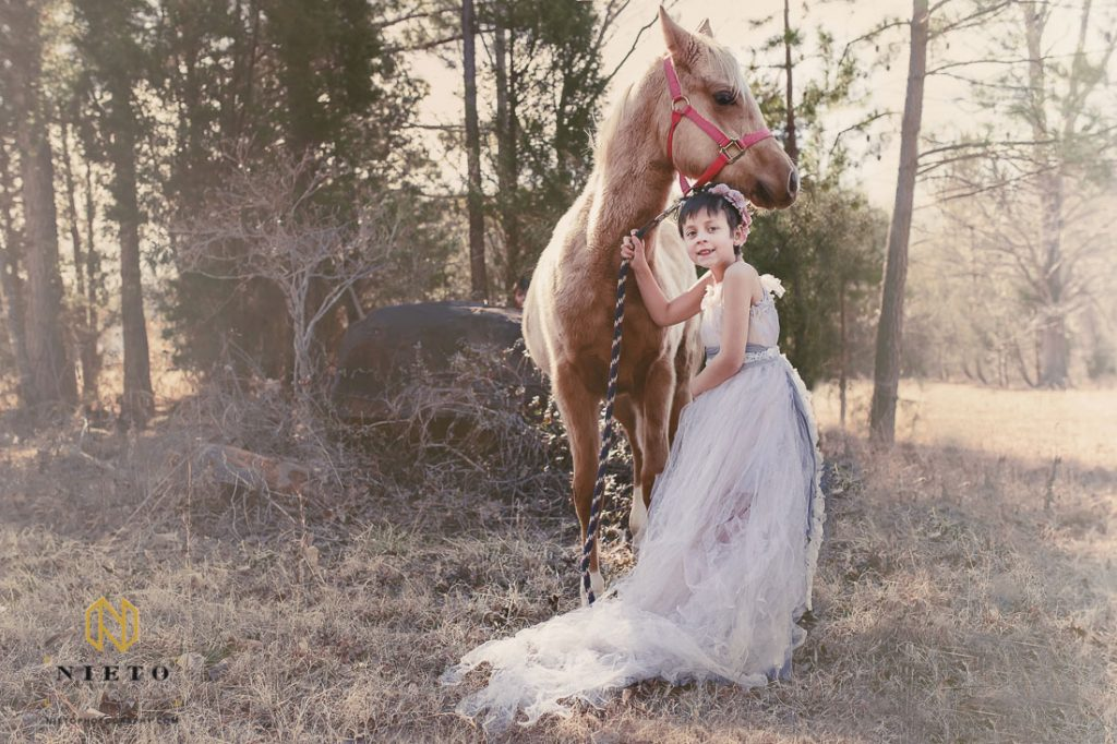 Little girl dressed in airy pink gown while standing beside her horse