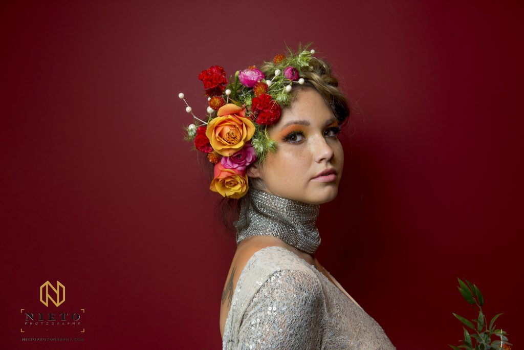 model on red background with flowers in har and silver dress