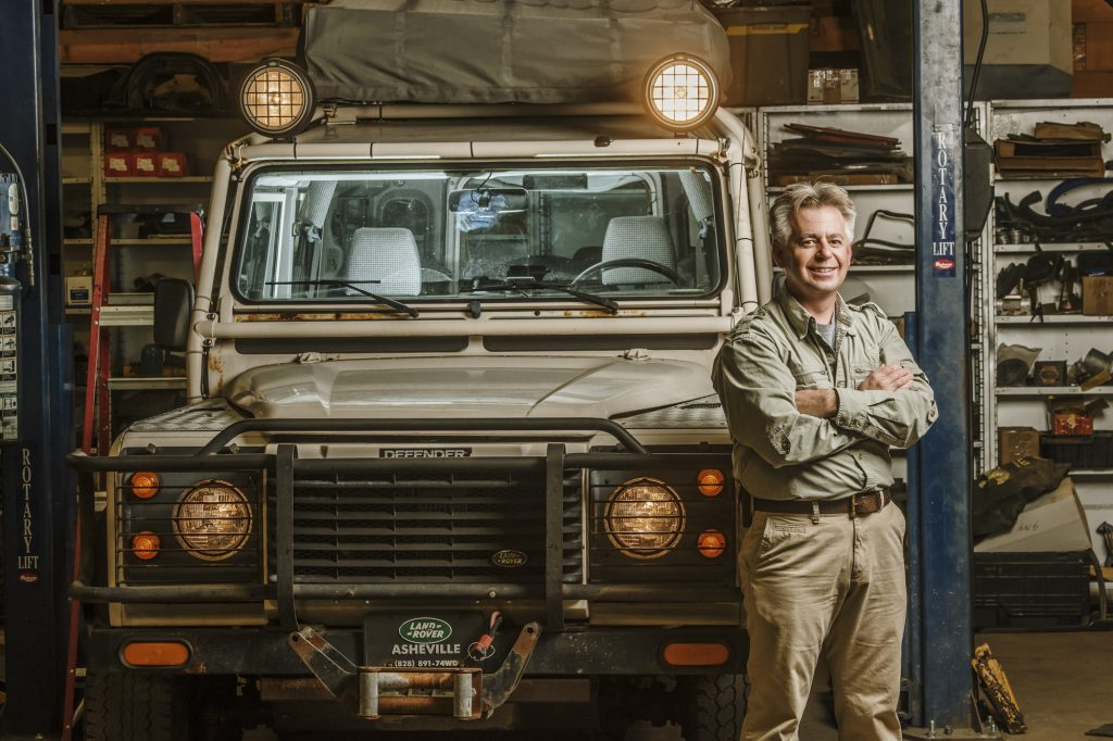 Man leaning and smiling against a Landrover defender