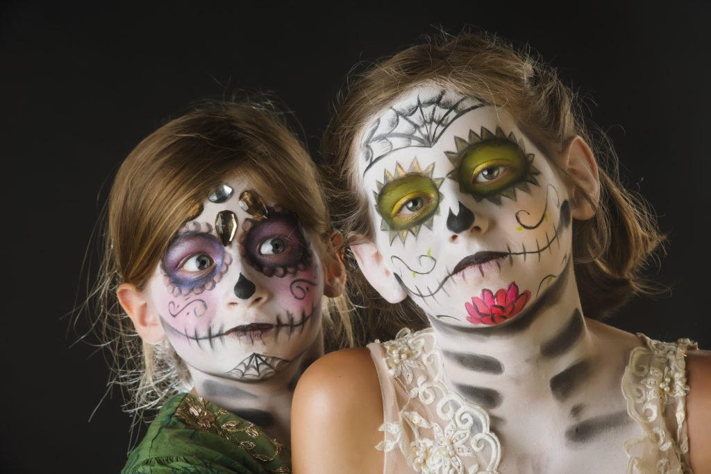 two little girls in sugar skull make up for day of the dead one smiling one not