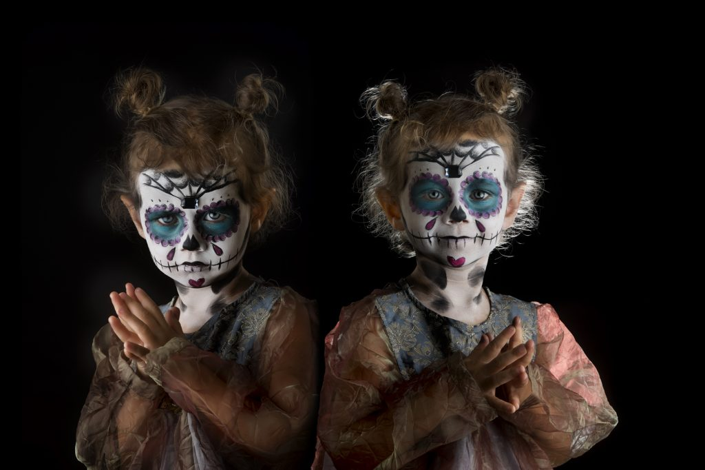 two images of a little girl in sugar skull make up for day of the dead with a sad and happy face