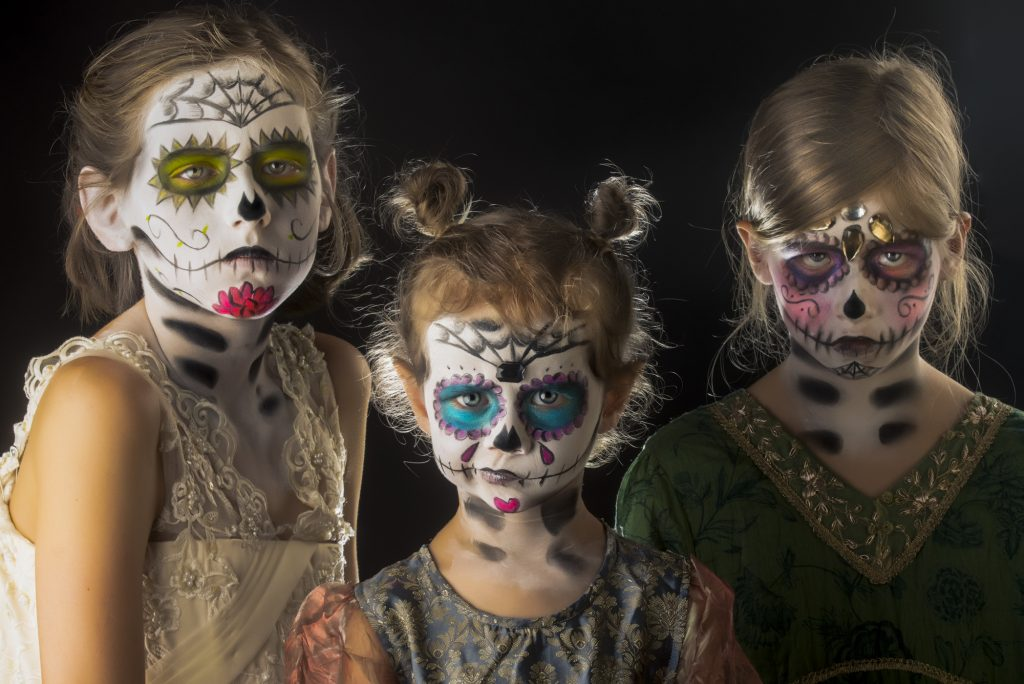 Three young girls posing for camera in sugar skull day of the dead make up with different expressions on their face