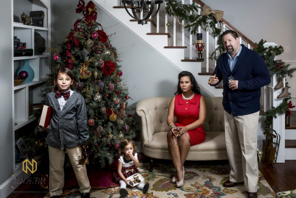 Family poses for very serious christmas picture in living room
