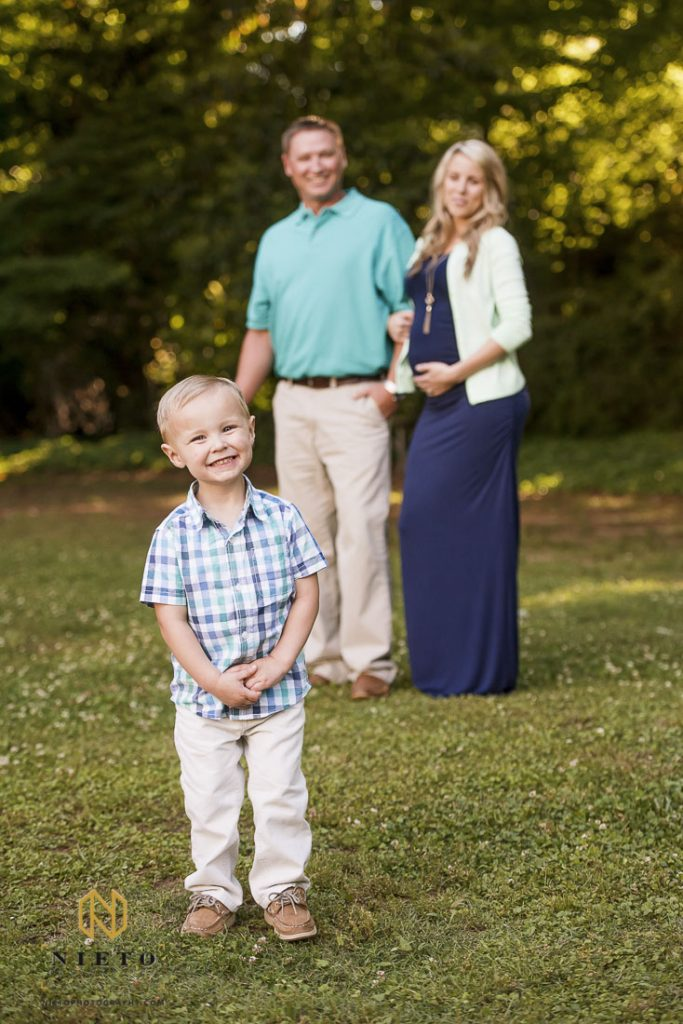 Little blonde boy smiling very big for camera as his mother and father stand behind him
