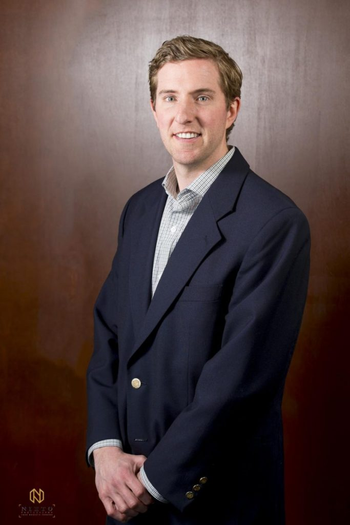 Lawyer posing infant of brown wall for headshot