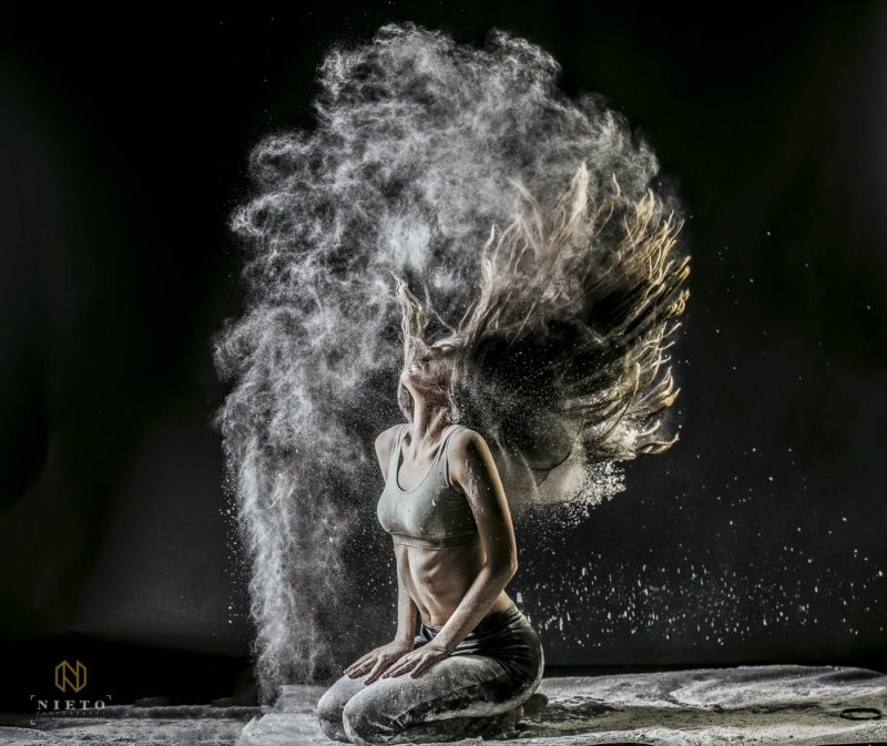 dancer throwing her hair back with flour and dust flying out