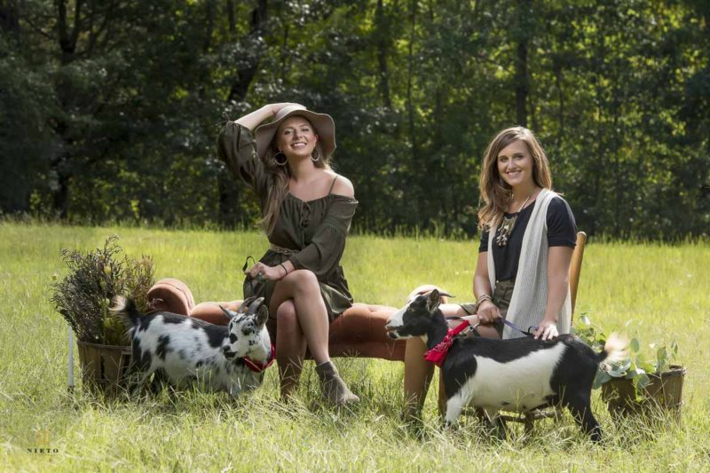 two women buisness owners pose with two pygmy greats in a field