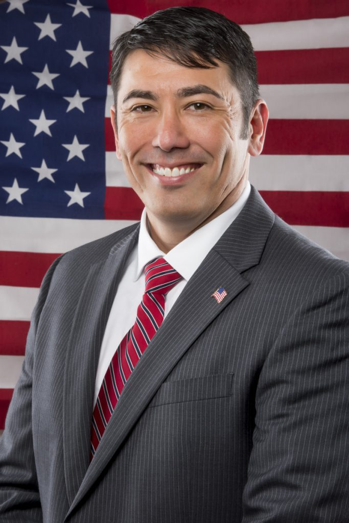 real estate agent posing for studio headshot in front of the American flag
