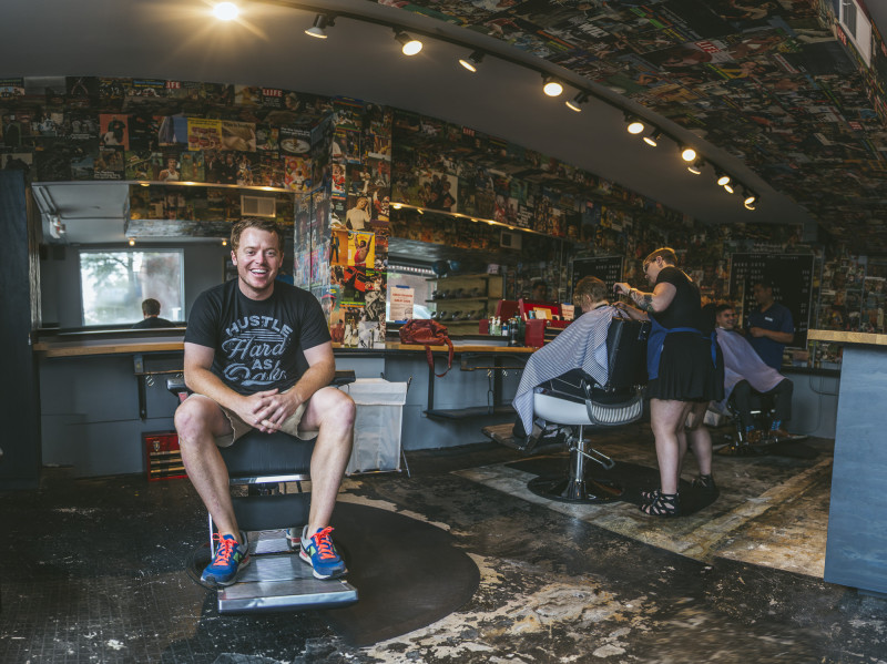 Buisness owner sits in barbers chair