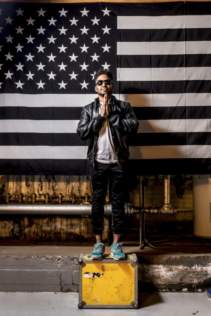 Dj posing in front of a Black and White american flag