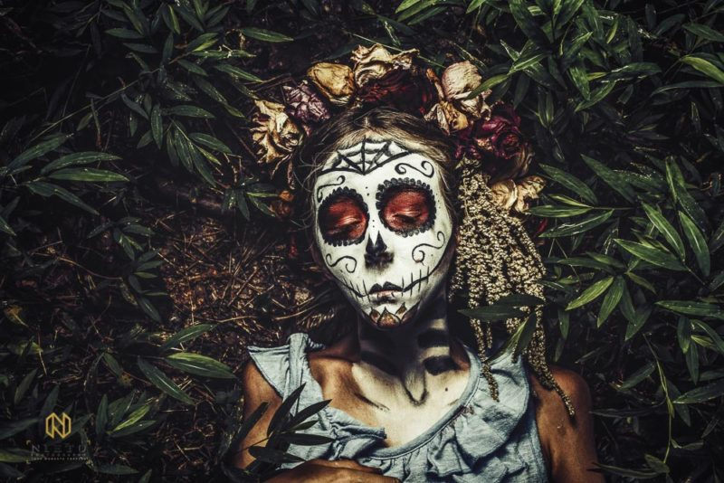 little girl with sugar skull makeup on laying on the grown making a sad face with her eyes closed