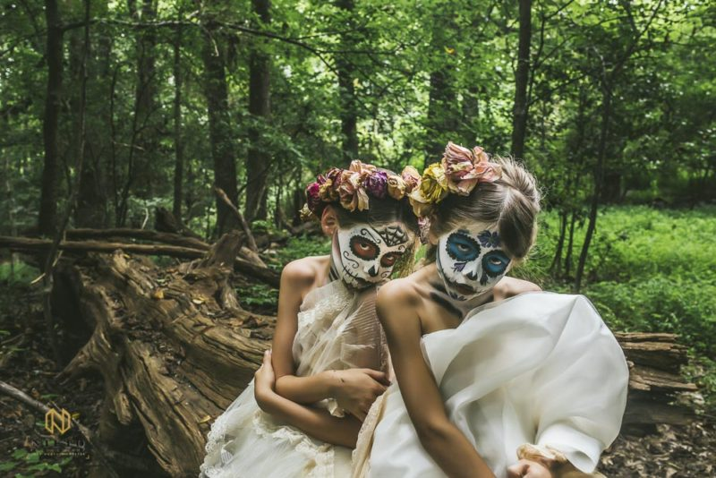two girls sitting on a log with sugar skull makeup on and dead flowers in their hair