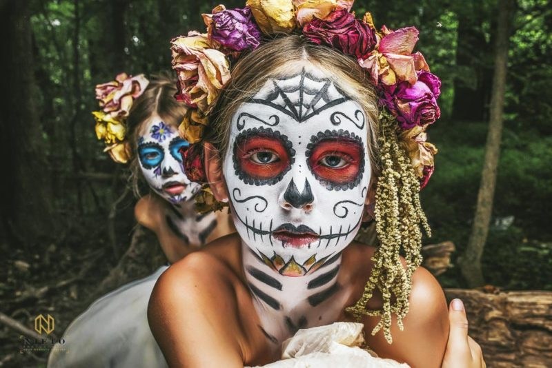 portrait of a girl with red sugar skull makeup and dead flowers in her hair and another girl behind her with blue makeup