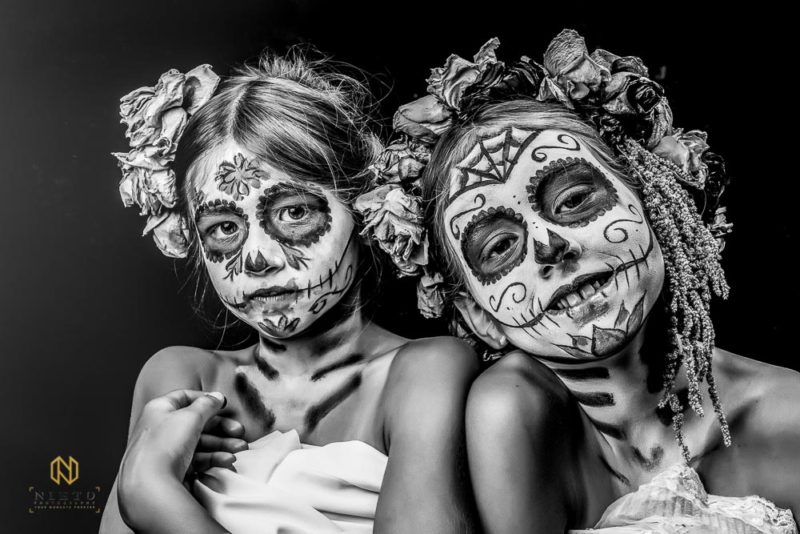 black and white image of two girls with sugar skull make up on one smiling the other not