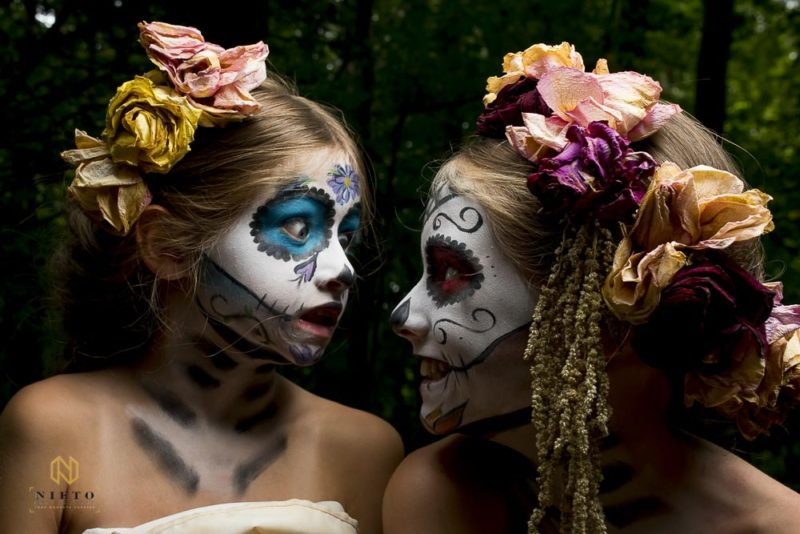 two little girls with sugar skull make up making faces at each other