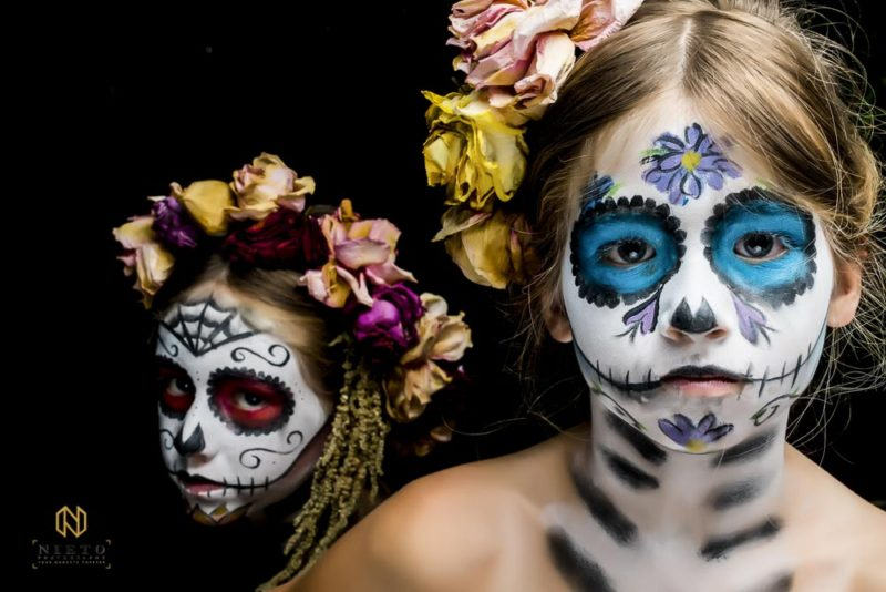 two girls with sugar skull makeup on one with blue and the other with red make up