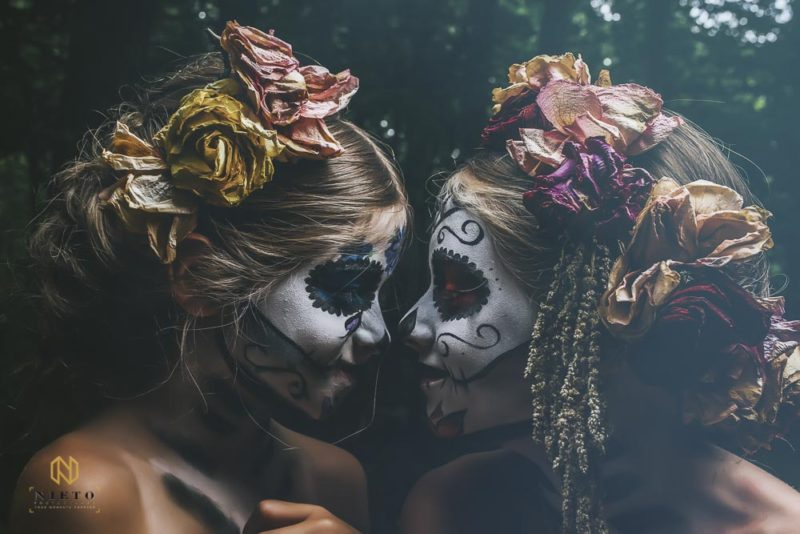 two girls with sugar skull makeup and flowers in their hair looking at each other and smiling