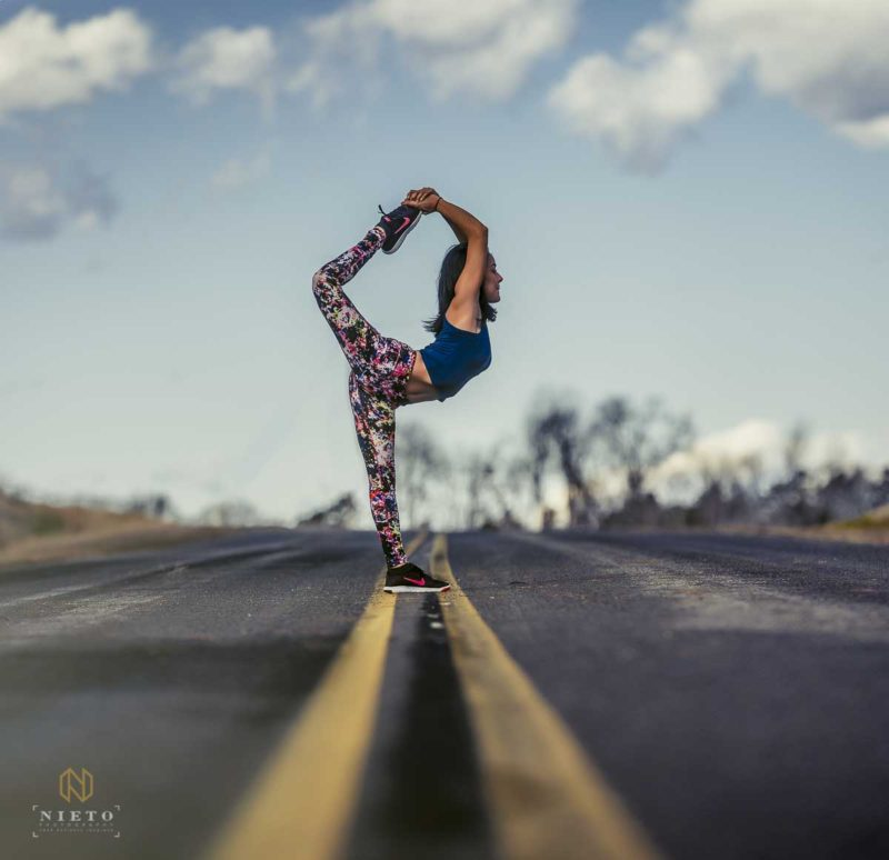 maggi zam of flower yogis standing in the road in Natarajasana pose