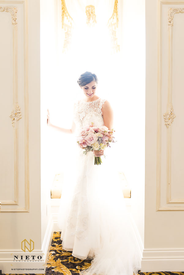 bride posing in the sunlight looking at her flowers
