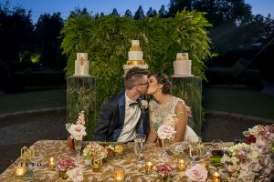 bride and groom kissing at sweetheart table at the Hall and Garden at Landmark