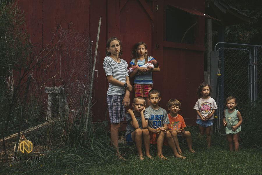 eight children standing in front of a chicken coop looking stoic