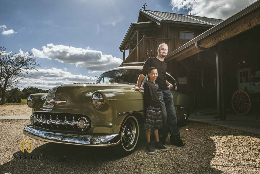 Father and son standing beside a green chevy belair