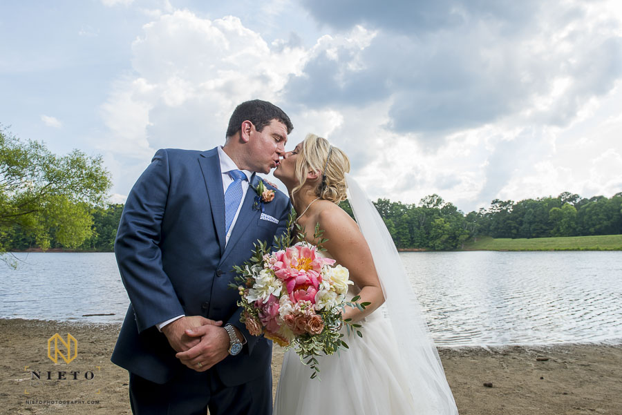 bride and groom kissing in front of bond lake in cary nc