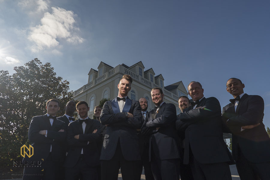 Groom and his groomsmen outside of the landmark posing for a group portrait