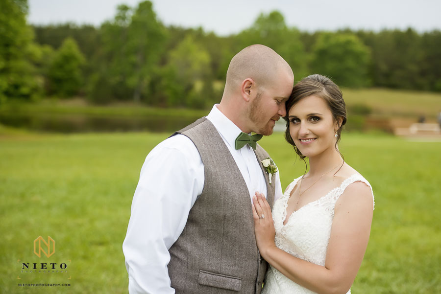 groom leaning his head into his bride while she smiles for the camera