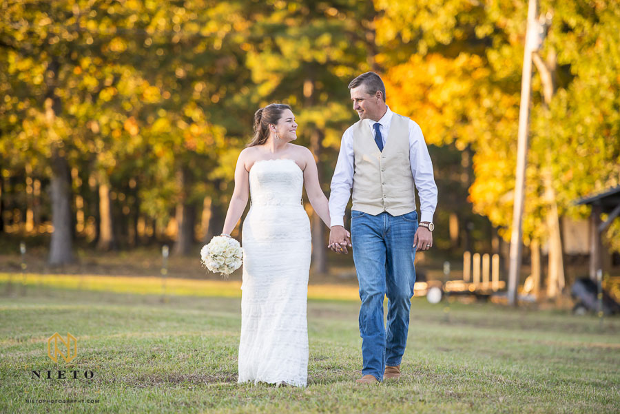 Couple walking in field with fall colors in the background