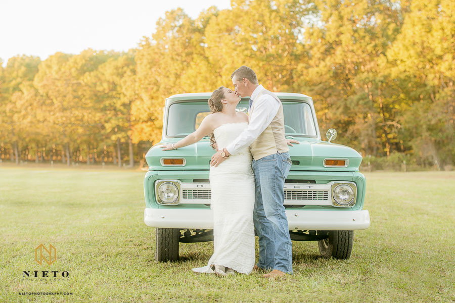 bride and groom kissing infant of their aqua marine antique truck in the middle of their wedding reception field