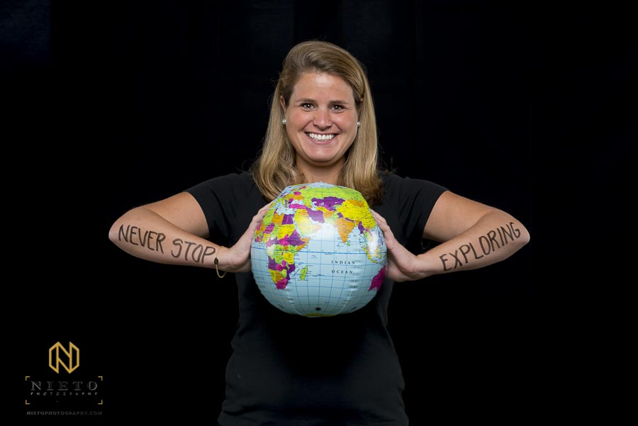 Woman holds inflatable globe while posing for portrait